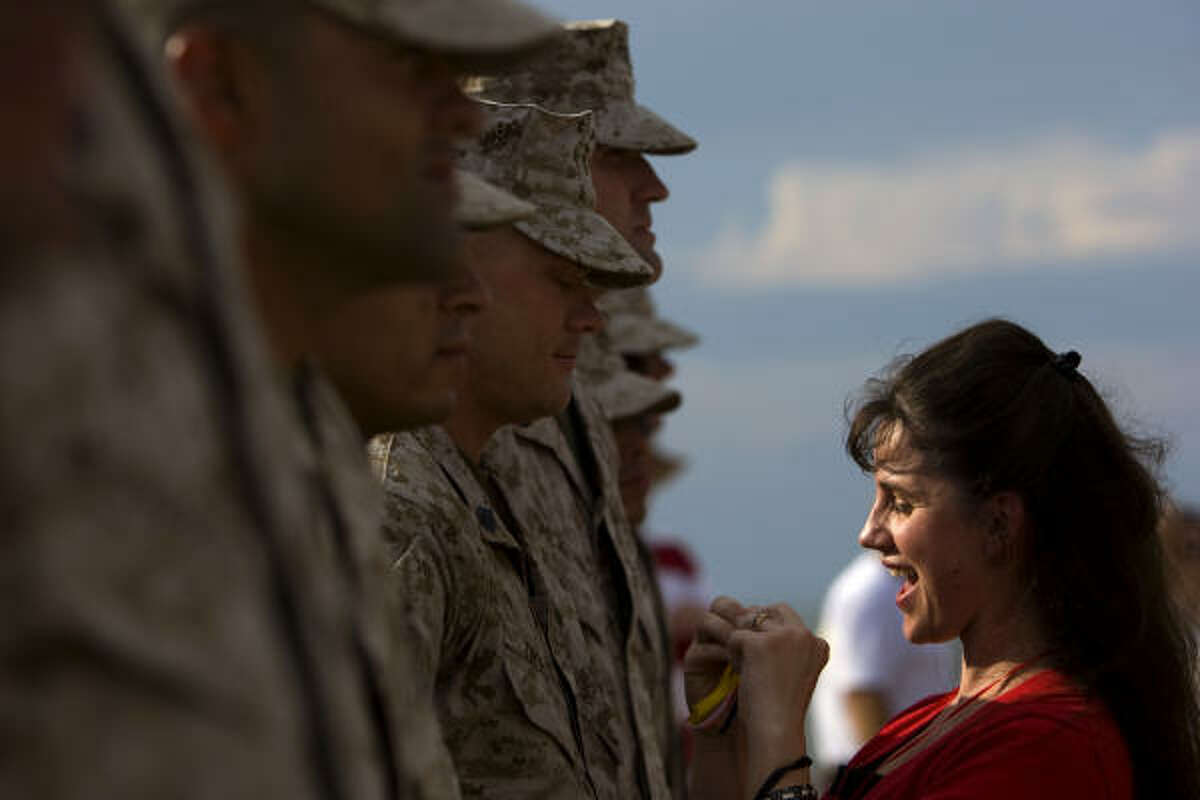 Shauna Dickey of Cleveland puts a Marine Corps Operation Iraqi Freedom pin on her husband, Staff Sgt. James Dickey, upon his return.