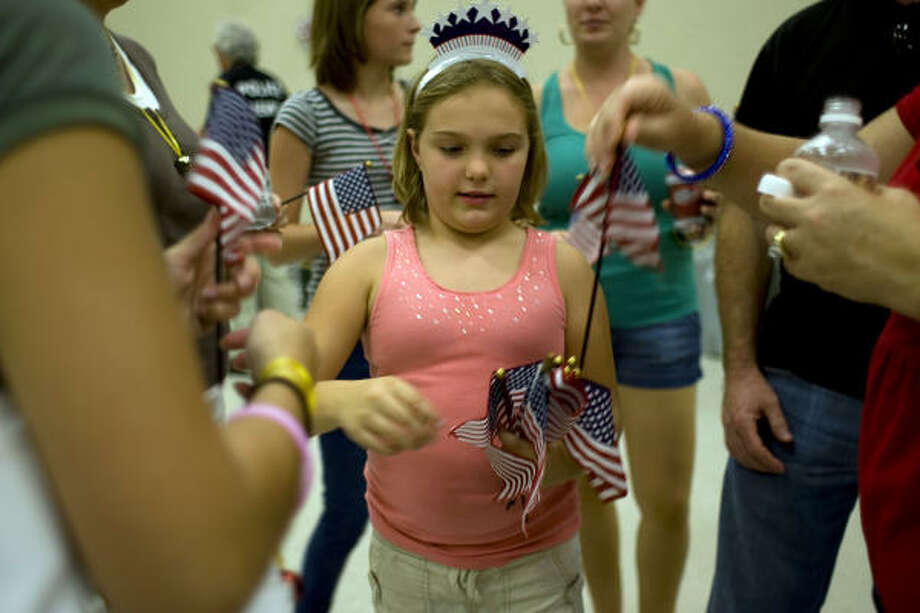 Tavin Wampler, 8, niece of Marine Cpl. Ryan Wampler, 24, of Katy hands out mini American flags as she waited for him and other Marines. Photo: Johnny Hanson, Chronicle