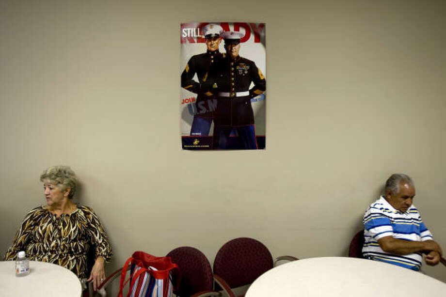 In a cafeteria at the Marine Reserve Training Center, Helen Studdard, left, of New Caney waits for her son-in-law Cpl. Daniel Edwards, and Gregorio Toriz of Eagle Lake waits for his son Cpl. Roger Toriz. Photo: Johnny Hanson, Chronicle