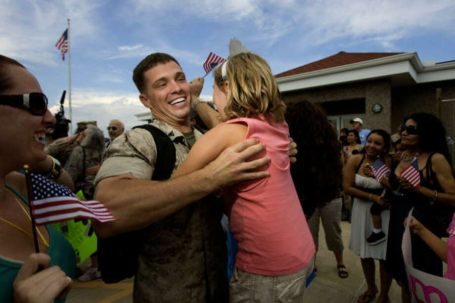 Cpl. Ryan Wampler, 24, of Katy is greeted by his niece, Tavin Wampler, 8, and other family members. Photo: Johnny Hanson, Chronicle