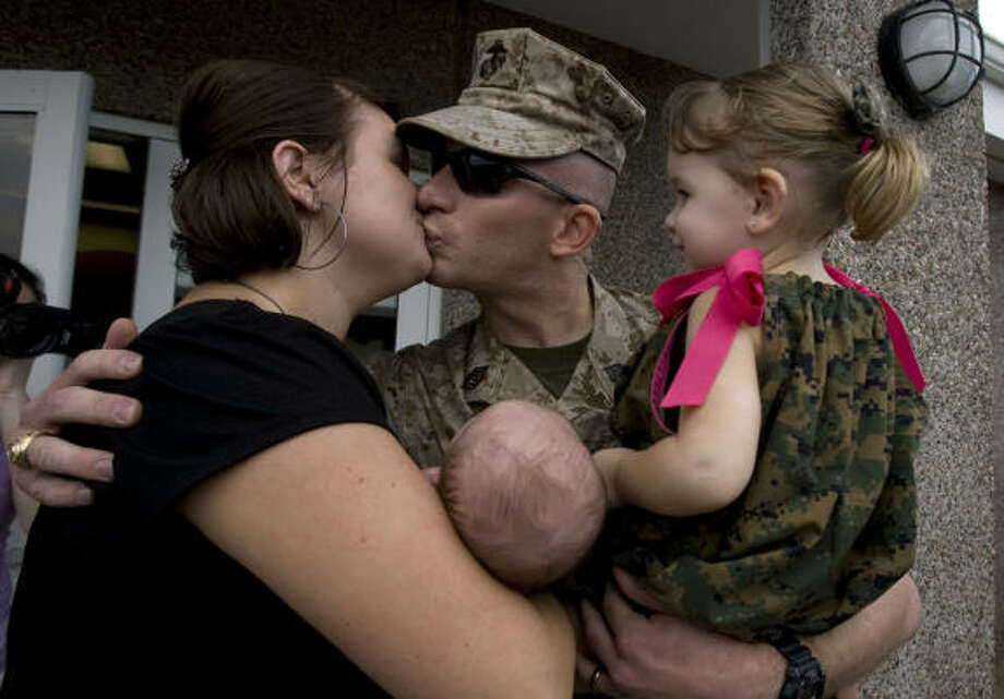 Gunnery Sgt. Matthew Lockwood is greeted by his wife, Shawna Lockwood, 26, daughter Abigail, 2, and his 6-week old son, Jackson. Photo: Johnny Hanson, Chronicle