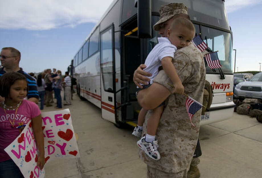 Staff Sgt. Matthew McKenney of New Caney holds onto his son Tayton, 2. Photo: Johnny Hanson, Chronicle
