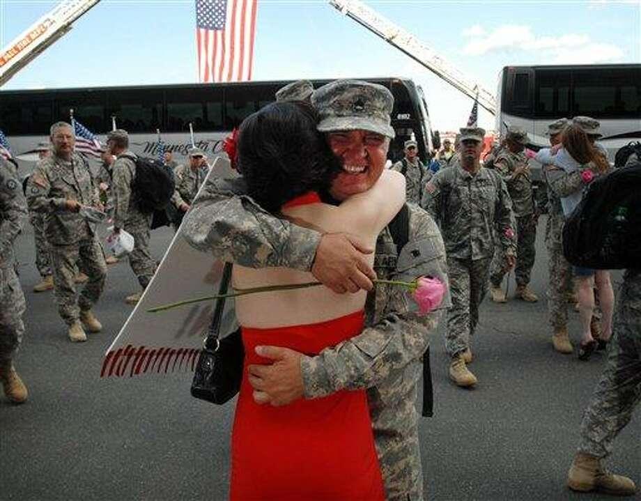 Staff Sgt. Dan Anderson hugs his wife, Susan Levine. Photo: Chris Polydoroff, AP