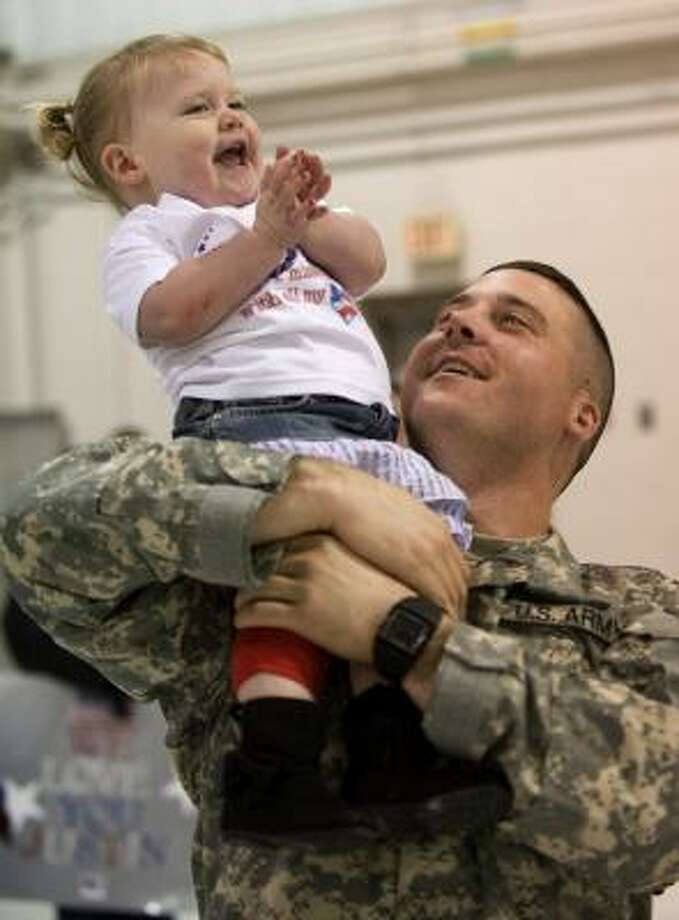Who: Spc. Kiel Bragg Where:   the Kentucky Air National Guard base in Louisville  When:  Feb. 15 Details:  Bragg holds his daughter Bailee, 2, at a homecoming ceremony. Photo: David R. Lutman, AP