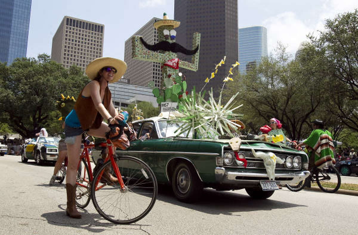 Art car artist Megan Casillas, front, waits for the parade to start again as she rides with her car