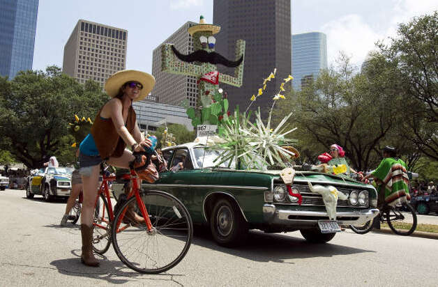 "Art car artist Megan Casillas, front, waits for the parade to start again as she rides with her car ""A Tribute to the Desert."" Photo: Nick De La Torre, Chronicle / HC"