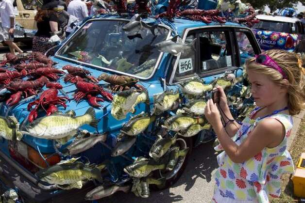 "Ava Grace Sweitzer, 6, takes a picture of her favorite art car, ""The Singing Fish Car."" Photo: Nick De La Torre, Chronicle / HC"