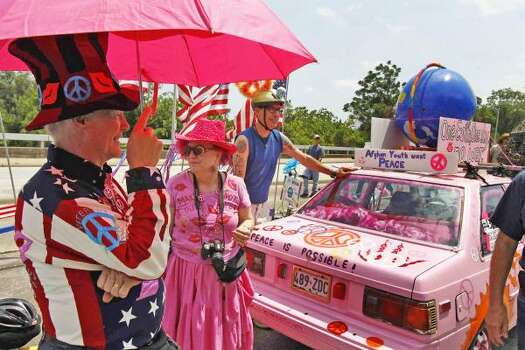 "Jim Williams of Vets for Peace visits an anti-war art car called ""Code Pink Peace Mobile"" before the parade. Photo: Nick De La Torre, Houston Chronicle"