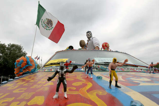 "Jesica Hano Hano and Todd Bowers look out the moon roof of their 'Lucha Mobile"" which is covered in a wrestling motif. Photo: Nick De La Torre, Houston Chronicle / HC"