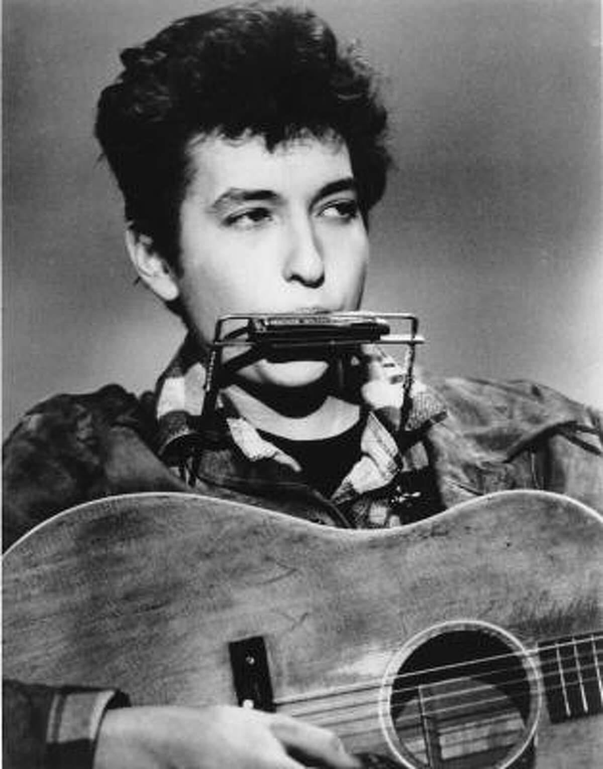 The answer, it turns out, is blowing into a harmonica. Dylan the young folkie in 1963.