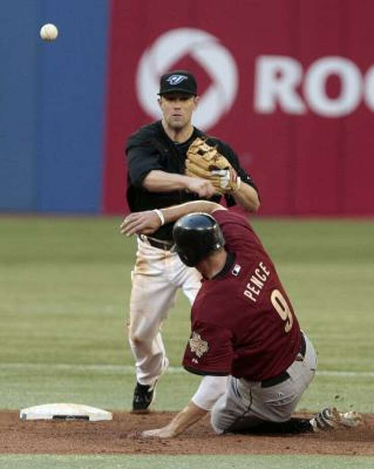 Blue Jays second baseman Aaron Hill turns a double play over a sliding Hunter Pence. Photo: Abelimages, Getty