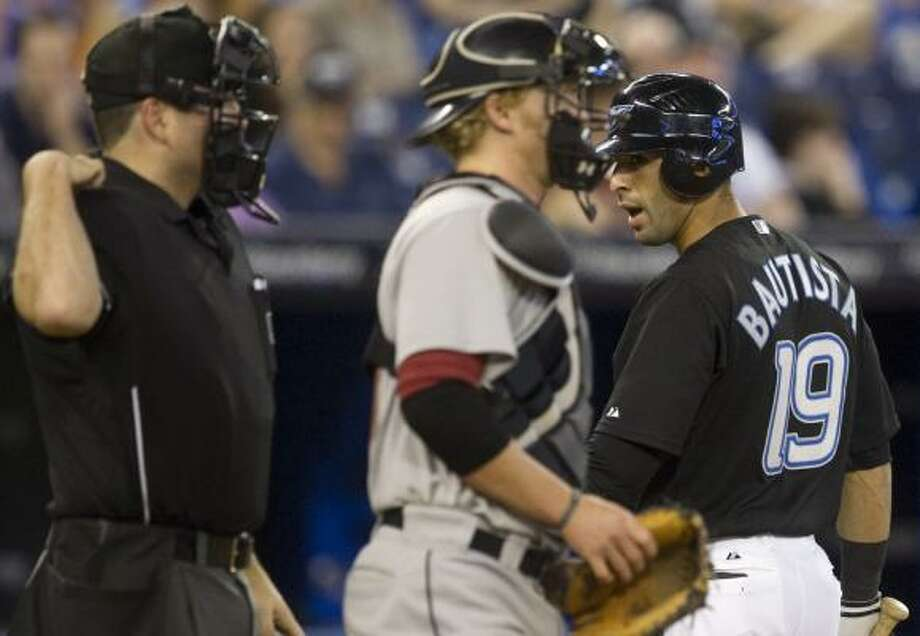 Blue Jays right fielder Jose Bautista argues with home plate umpire Dan Bellino after being struck out by Wandy Rodriguez. Photo: Darren Calabrese, Associated Press