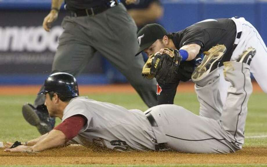 Blue Jays third baseman Jayson Nix tags out Astros first baseman Brett Wallace at third base during eighth inning. Photo: Darren Calabrese, Associated Press