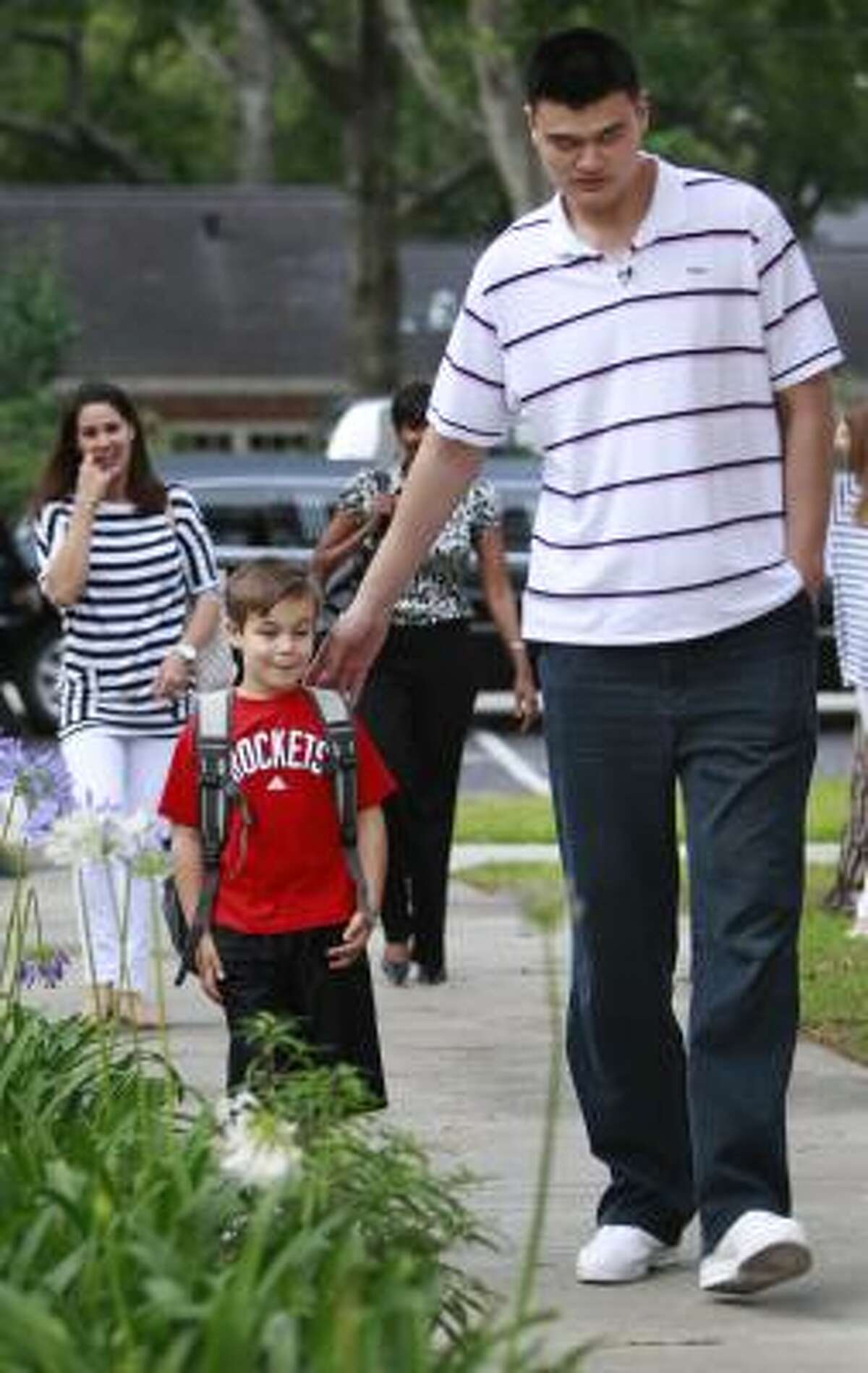 First-grade student Jackson Loyd escorts his guest, Yao Ming, to his school.