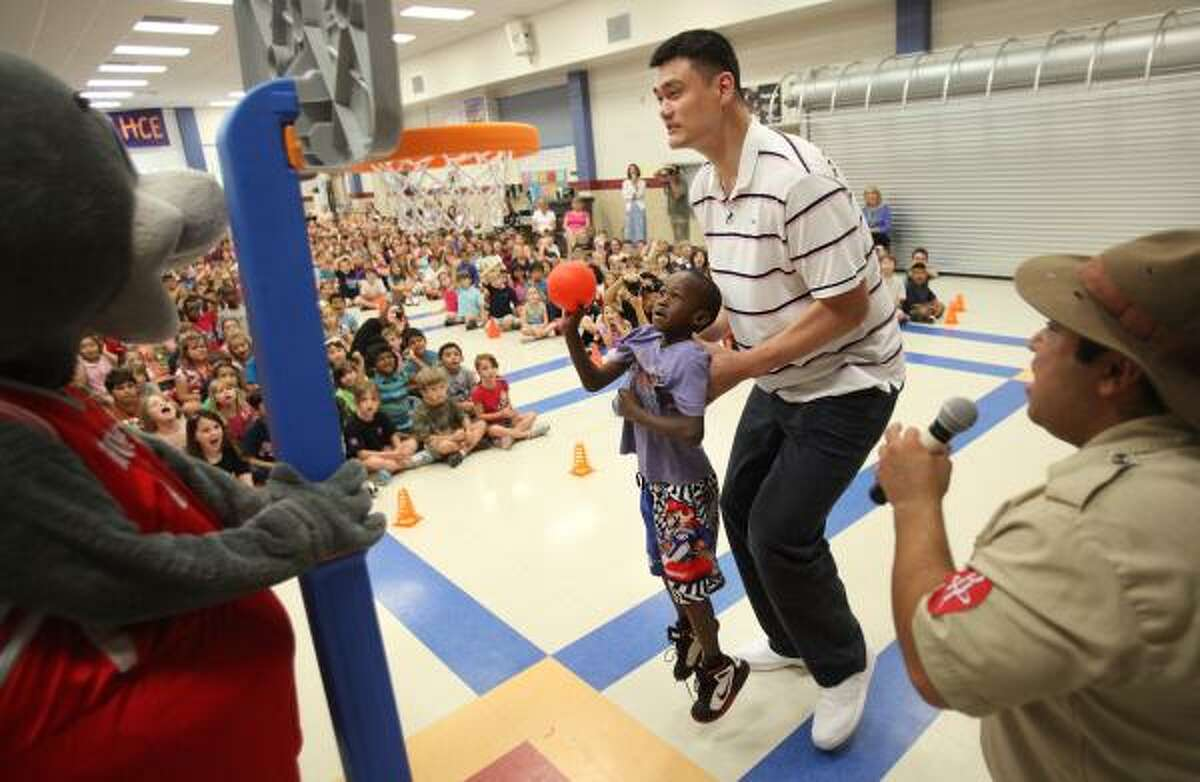 James Kangethe is lifted by Yao Ming to slam dunk during Yao's appearance at Hunters Creek Elementary.