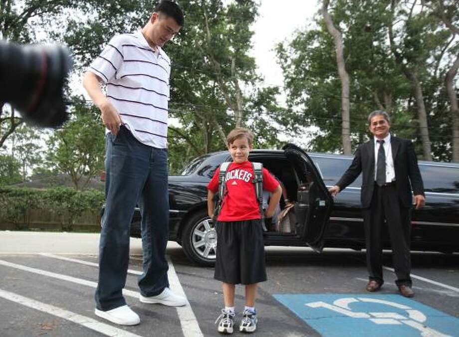 Rockets center Yao Ming and first-grader Jackson Loyd arrive to school in a limo as Yao visits Hunters Creek Elementary School. The Loyd Family purchased the opportunity to bring Yao to school during the Rockets' 2011 Tux and Tennies Gala held in March. Photo: Mayra Beltran, Chronicle