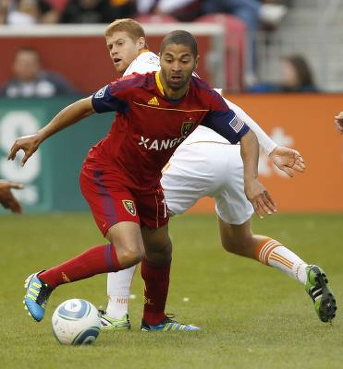 Real Salt Lake's Alvaro Saborio, front, takes the ball from Dynamo defender Andrew Hainault.