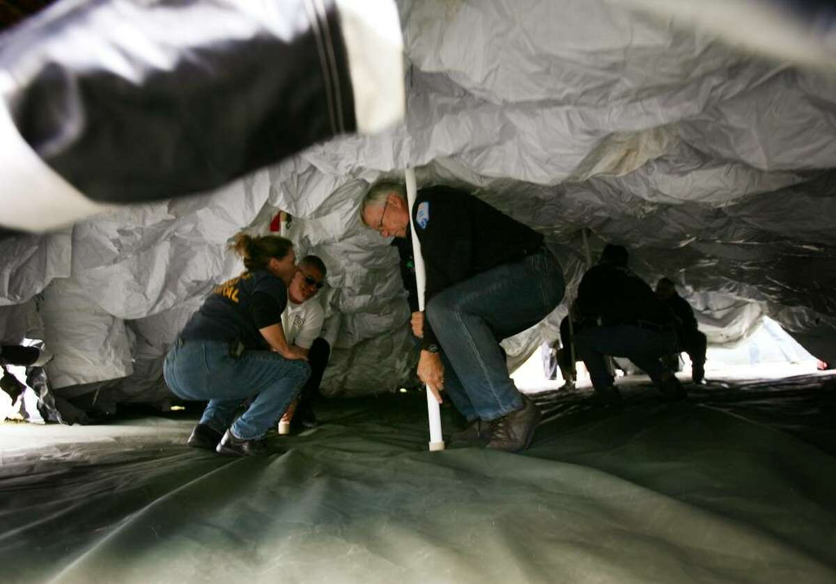 From left; Department of Public Health nurse Mary Emerling, directs EMTs Doug Morrison of Westport EMS, Sherman Turner of Easton EMS, and others to erect a mobile field hospital tent at the Fairfield Fire Training Center on Thursday, October 1, 2009 in Fairfield, Conn.