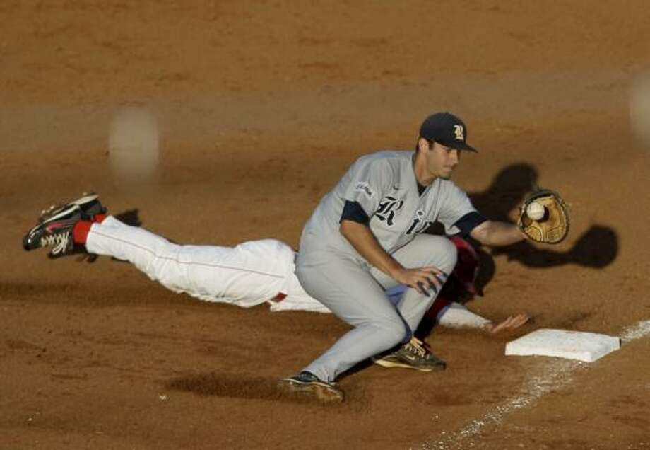 UH's Joel Ansley dives back to first base before Rice first baseman J.T. Chargois can apply the tag in the second inning. Photo: Thomas B. Shea, For The Chronicle