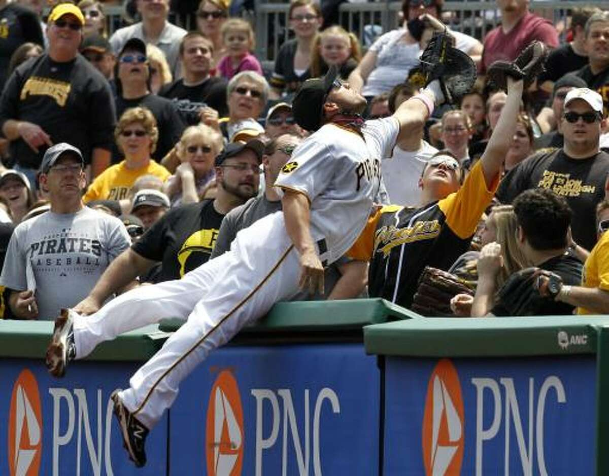 Pirates first baseman Steve Pearce leaps into the stands in an attempt to catch a foul ball during the second inning.