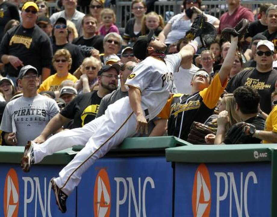 Pirates first baseman Steve Pearce leaps into the stands in an attempt to catch a foul ball during the second inning. Photo: Gene J. Puskar, Associated Press