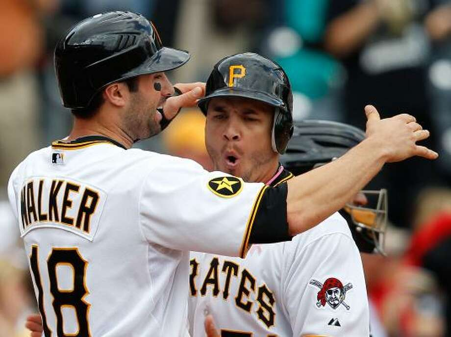 Pirates first baseman Steve Pearce, center, celebrates with second baseman Neil Walker after catcher Ryan Doumit hit a three-run home run. Photo: Jared Wickerham, Getty