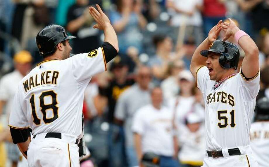 Pirates first baseman Steve Pearce high fives second baseman Neil Walker after they scored on a homer in the eighth. Photo: Jared Wickerham, Getty