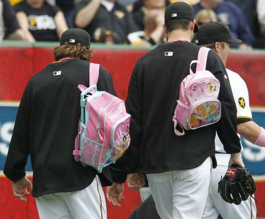 Pirates rookie pitchers Daniel Moskos, left, and Mike Crotta carry their pink backpacks to the bullpen before the game. Photo: Gene J. Puskar, Associated Press