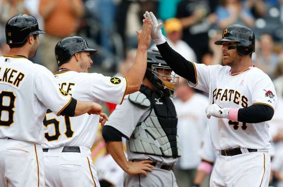 Pirates catcher Ryan Doumit greets his teammates at home plate after a three-run homer. Photo: Jared Wickerham, Getty