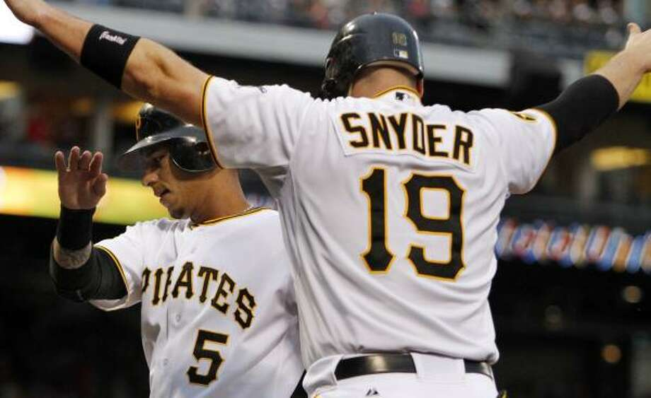 Pittsburgh's Ronny Cedeno (5) is greeted by Chris Snyder after both scored on a second-inning double by Andrew McCutchen. Photo: Gene J. Puskar, Associated Press
