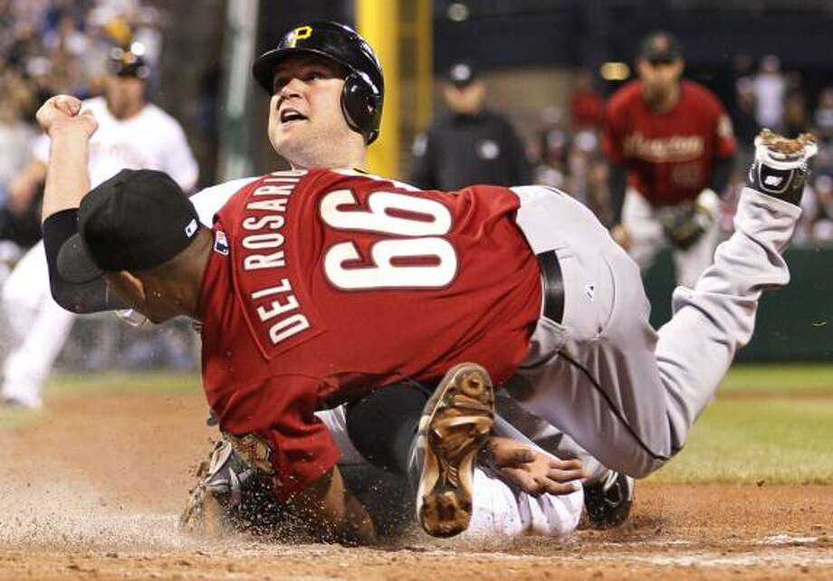 Pittsburgh's Chris Snyder, top rear, slides under the tag by Astros reliever Enerio Del Rosario to score on a wild pitch in the eighth inning. Photo: Gene J. Puskar, Associated Press