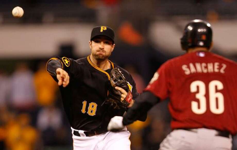 Pirates second baseman Neil Walker, left, attempts to turn the double play on Angel Sanchez. Photo: Jared Wickerham, Getty