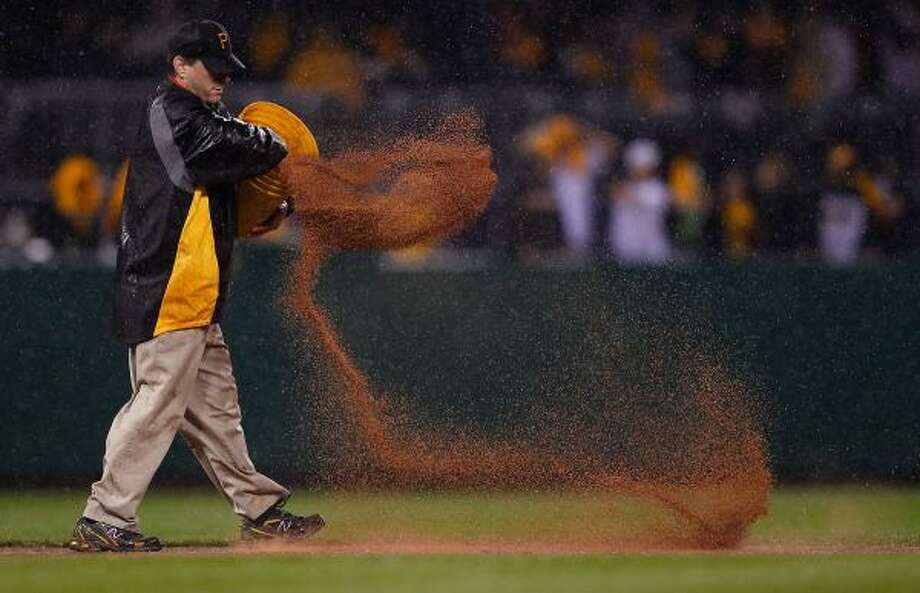 A member of the grounds crew puts down diamond dirt in the infield to soak up rain falling during Friday's game. Photo: Jared Wickerham, Getty
