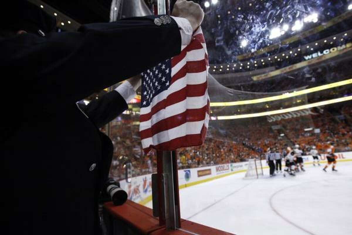 A Philadelphia Police officer holds up a U.S. flag during the first period in Game 2 of the Eastern Conference semifinal NHL Stanley Cup playoffs series between the Philadelphia Flyers and the Boston Bruins.