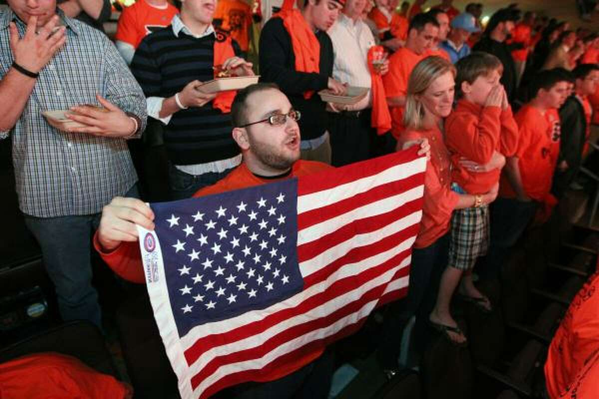 Robert Mayer holds an American flag while chanting U-S-A at the Wells Fargo Center on Monday.