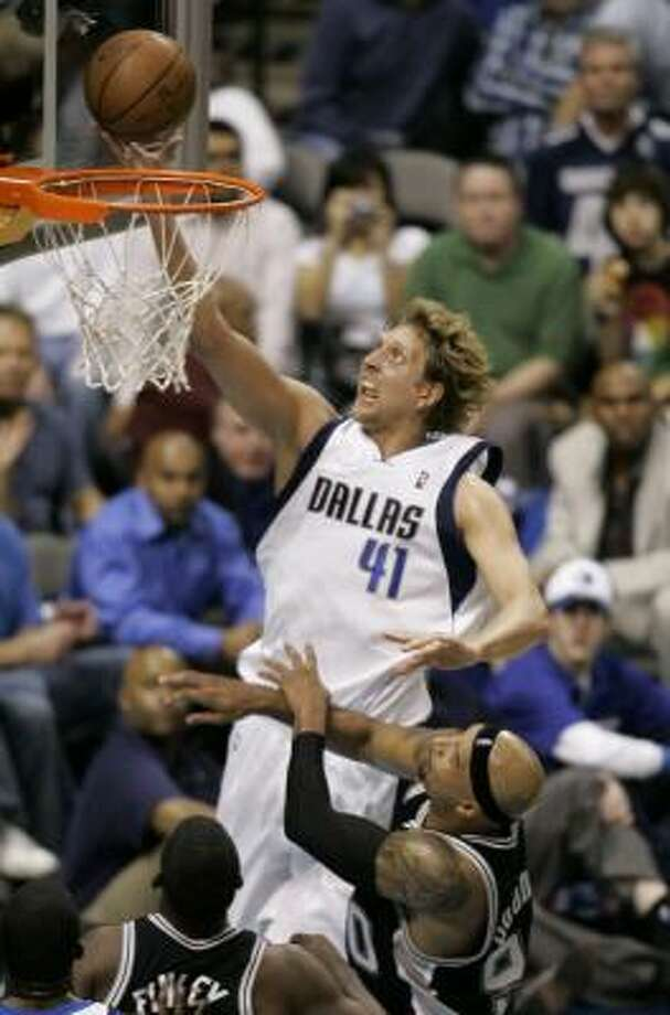 Mavericks forward Dirk Nowitzki attempts a layup over Spurs forward Michael Finley, center bottom, and Drew Gooden, right bottom, in the first half. Photo: Tony Gutierrez, AP