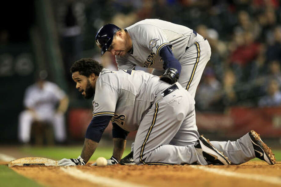 Milwaukee's Prince Fielder is checked on by Brewers first base coach Garth Iorg after colliding with Astros first baseman Brett Wallace during the seventh inning. Photo: Michael Paulsen, Chronicle