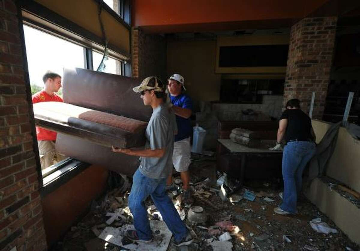Employees and their friends salvage furniture from a restaurant in a tornado stricken neighbourhood April 30, 2011 in Tuscalosa, Alabama. Residents are reeling from the worst US tornadoes in nearly 80 years.