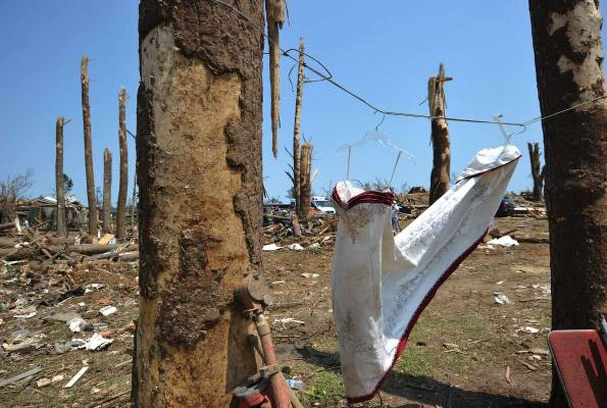 A salvaged gown is hung between trees in the tornado stricken Forest Lake neighbourhood April 30, 2011 in Tuscalosa, Alabama. Residents are reeling from the worst US tornadoes in nearly 80 years.