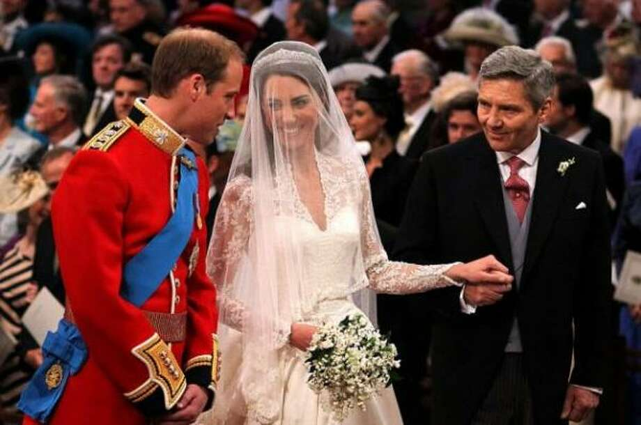 Prince William speaks to his bride as she holds the hand of her father.