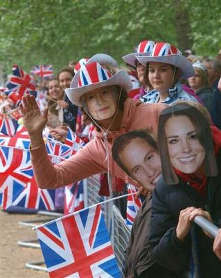 Royal fans wearing a  Kate Middleton mask, right, a Prince William mask, 2nd right, and a Queen Elizabeth mask wait on London's The Mall for the wedding cortege of Prince William and his bride to be Kate Middleton to pass by coming from nearby Westminster Abbey, Friday April 29, 2011, 2011. Photo: MAX NASH, AP