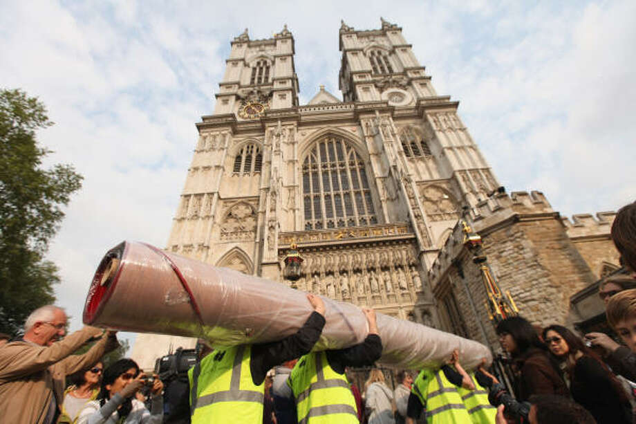 Workers carry in sections of the red carpet in front of Westminster Abbey. Photo: Sean Gallup, Getty Images