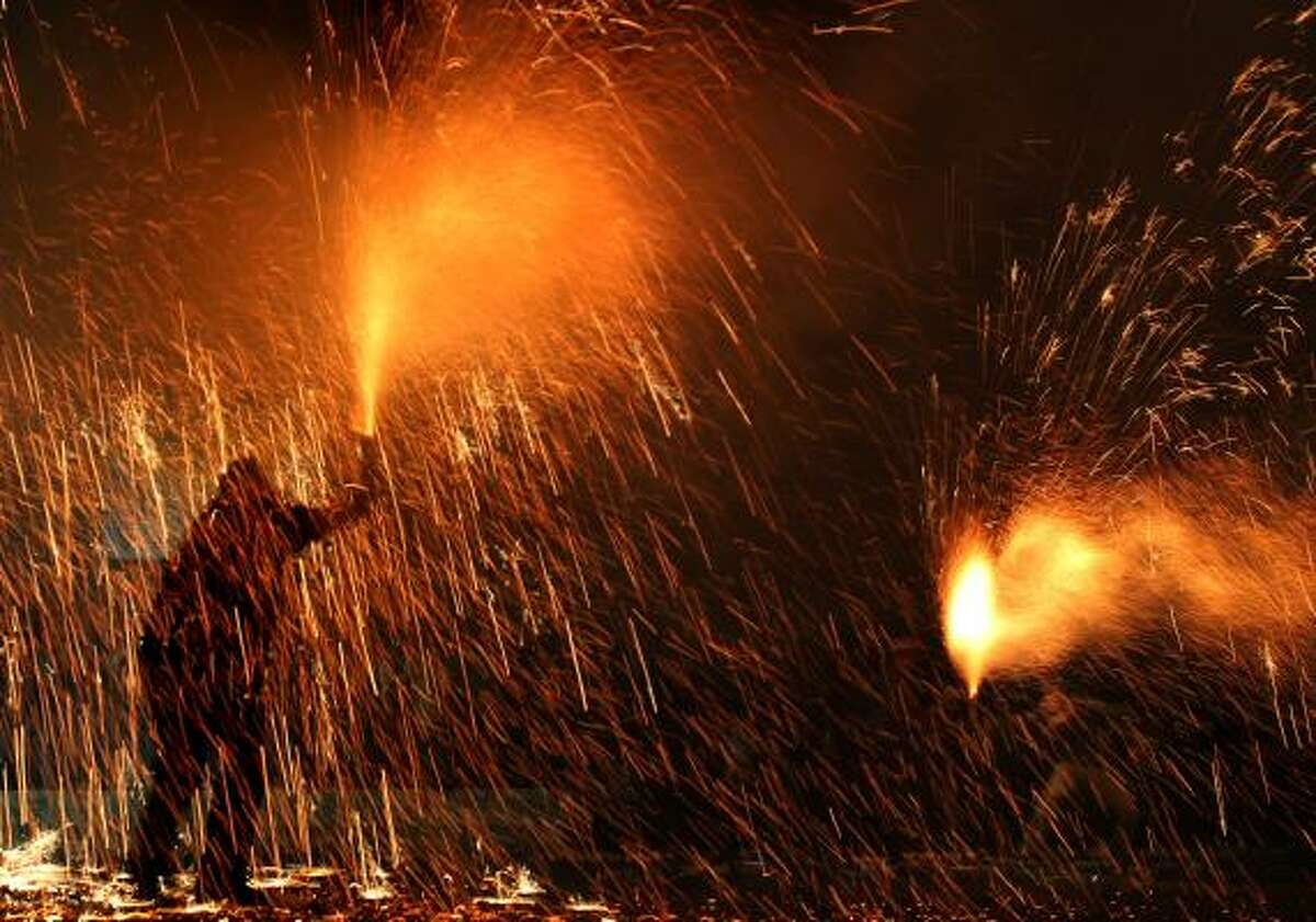 Revelers hold flares during pre-Easter celebrations in the city of Agrinio, western Greece, late Good Friday. The celebration, known as