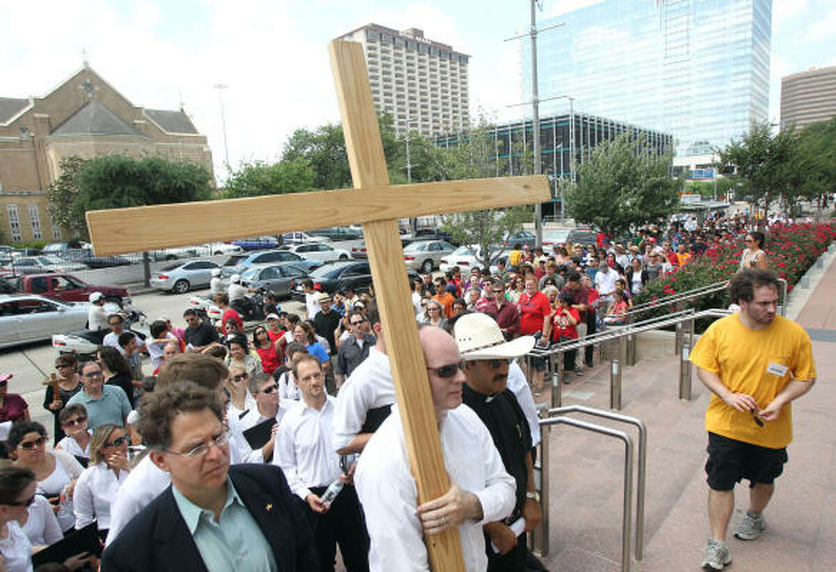 Abel Cruz carries the cross at the ending of The University of St.Thomas and Communion and Liberation Way of the Cross Good Friday procession in front of the Co-Cathedral of the Sacred Heart in Houston. The procession started at the St. Basil Chapel and ended at the Co-Cathedral.