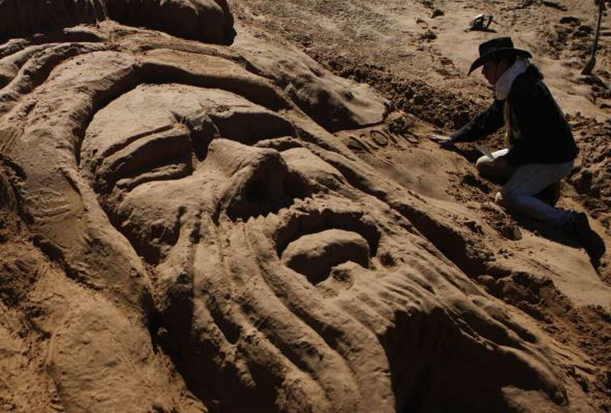 A man works on a sand sculpture depicting Jesus Christ during Holy Week in Arenal de Cochiraya, Oruro, Bolivia.