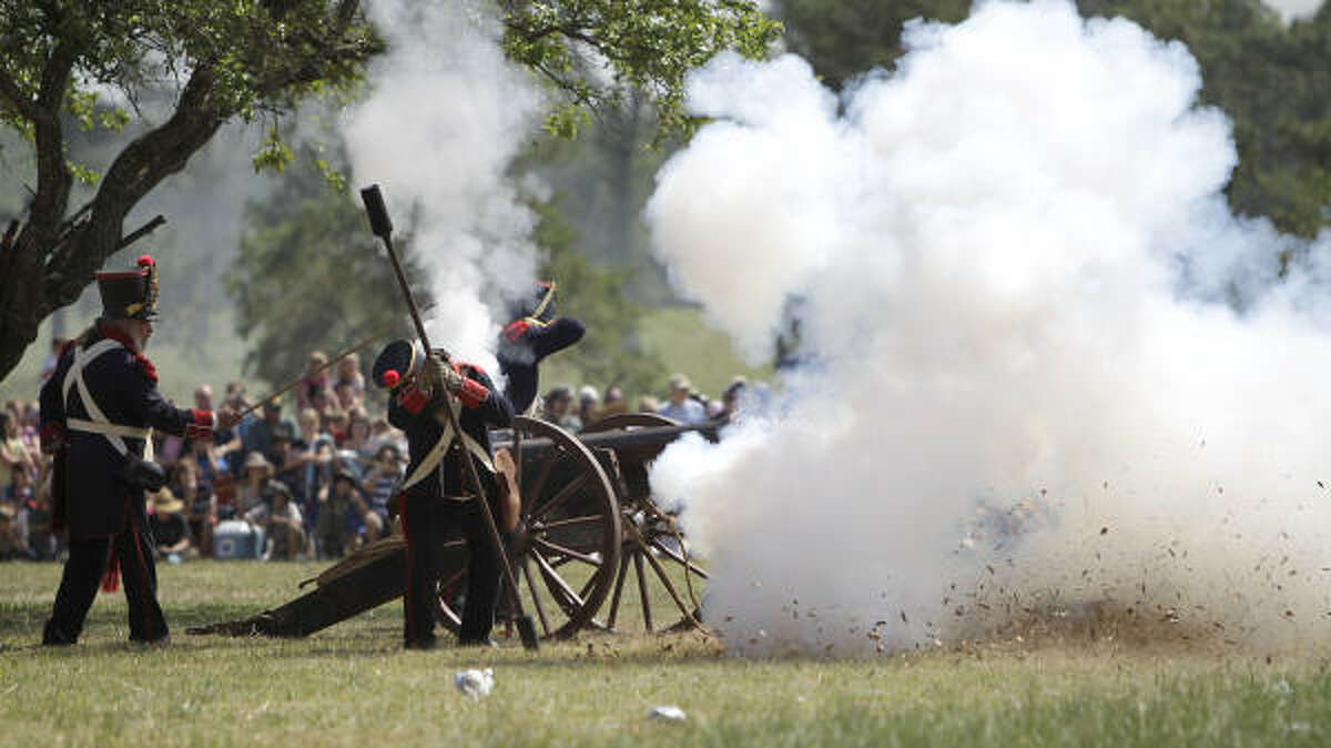 Re-enactors playing the parts of Mexican Army soldiers fire a canon.