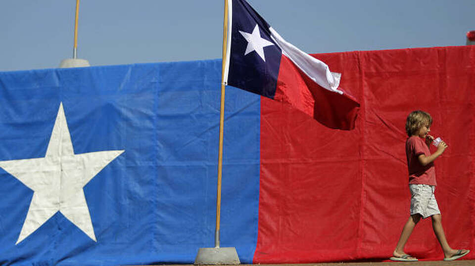 Travis Provence, 8, of Houston, sips a lemonade next to the Texas flag on the grounds of the San Jac