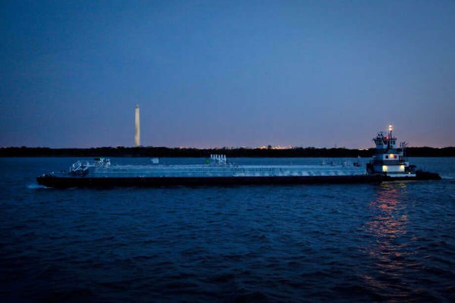 The San Jacinto Monument is seen through a barge passes on the Houston Ship Channel as night falls on Thursday, April 15, 2010. Photo: Smiley N. Pool, Chronicle