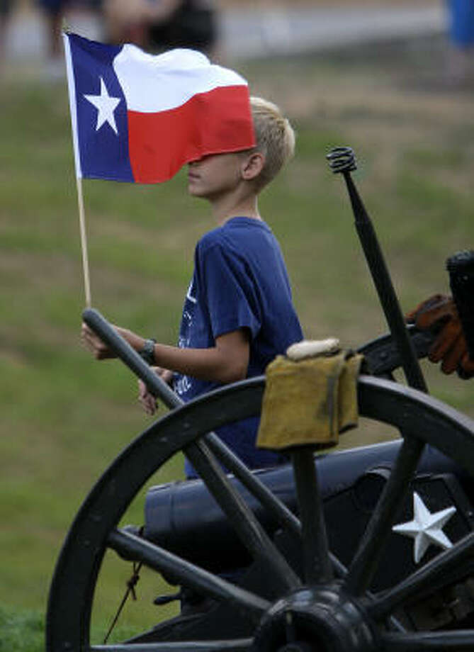 "Travis Bartlett, 9, of The Woodlands, holds a Texas flag as he stands next to ""Rolling Thunder"" the canon, during the Lone Star Monument and Historical Flag Park unveiling and dedication on the 175th anniversary of the Republic of Texas. Photo: Karen Warren, Houston Chronicle"