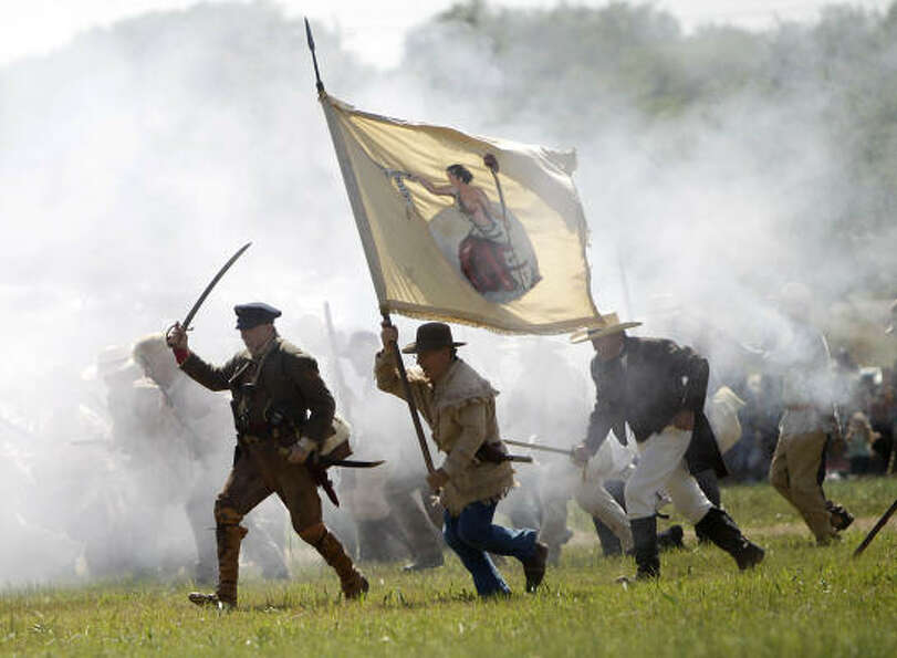 Re-enactors playing the parts of members of the Texian Army charge toward the Mexican encampment dur